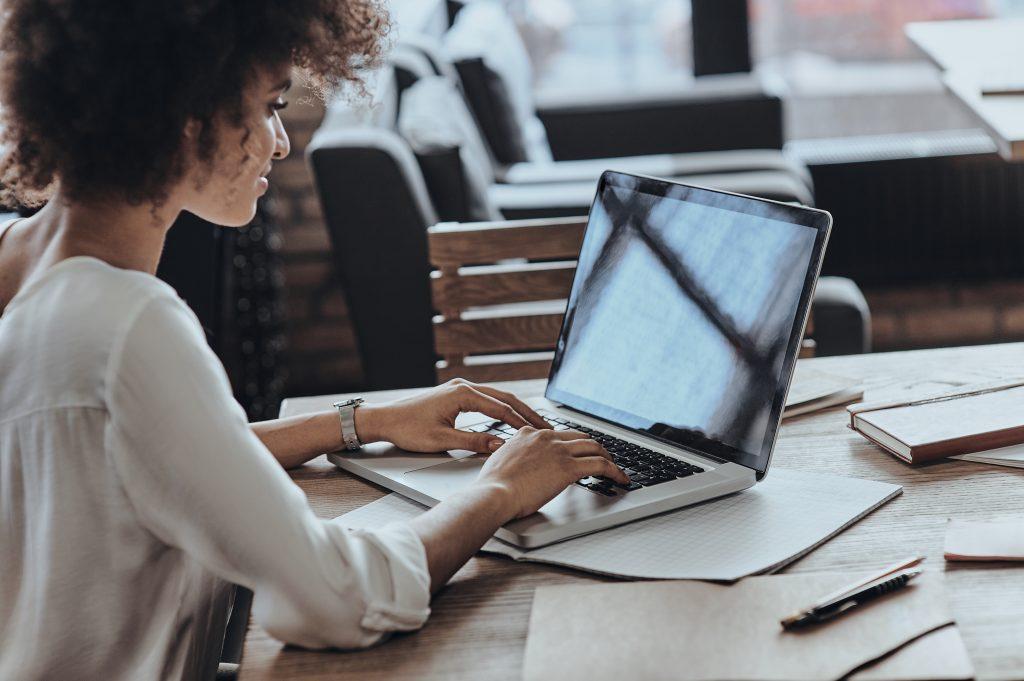 Mulher usando um Macbook na mesa com uma expressão leve