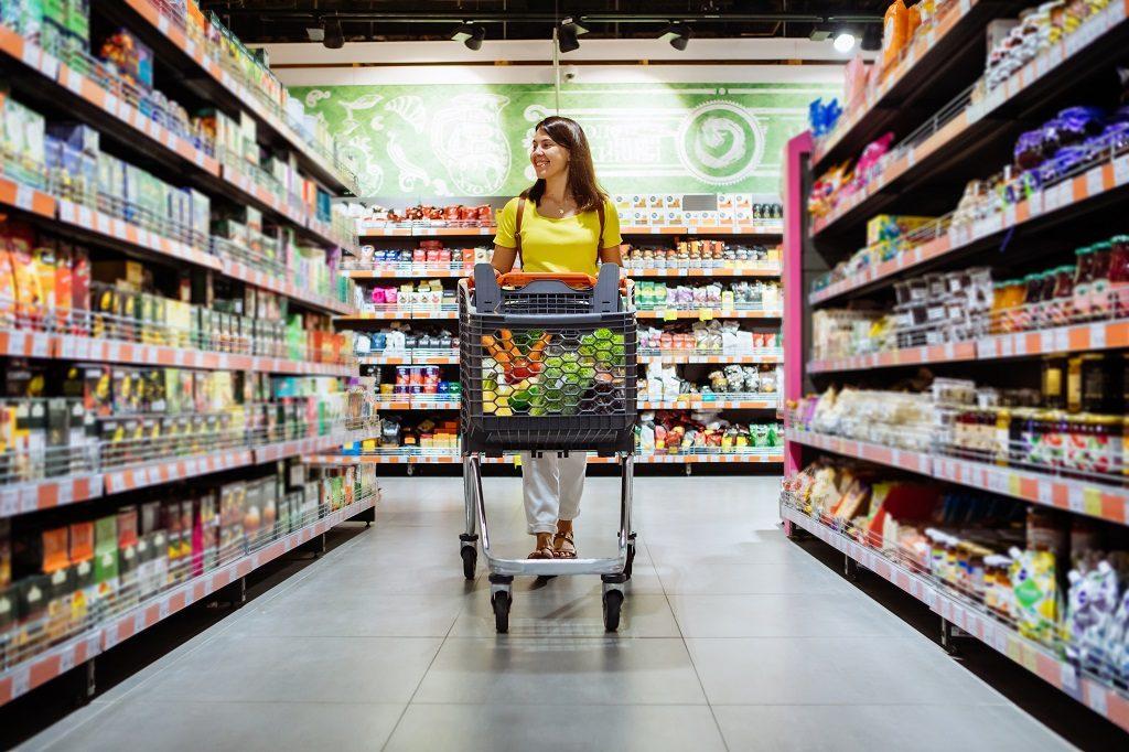 Mulher passeia por prateleiras do supermercado fazendo compras
